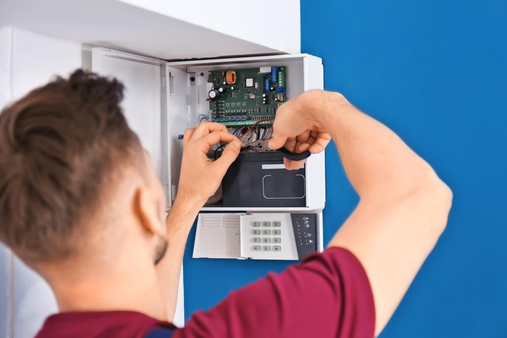 man fixing alarm system